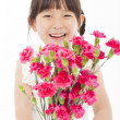 Close up of happy little girl holding a bouquet of carnations — Stock Photo