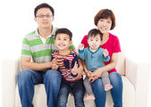 Happy asian  family sitting on a white leather sofa  — Stock Photo