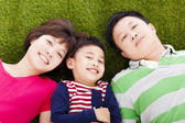 Happy parents and son lying on a meadow — Stock Photo