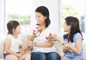 Two daughters handing mother carnations  — Stock Photo