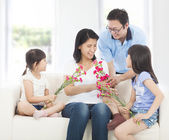 Daughters and father handing mother carnations  — Stock Photo
