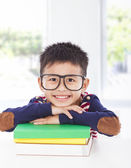 Smiling little boy lying on books  — Stock Photo