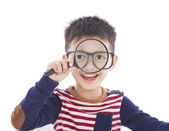 Adorable boy holding a magnifier and watching through — Stock Photo