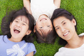 Happy mother and daughters lying on a meadow — Stock Photo