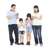 Family standing a row and using smart phone together — Stock Photo