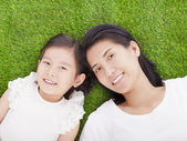 smiling mother and daughter lying on a meadow — Stock Photo