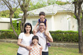 Happy family standing before their house — Stock Photo