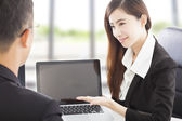 Smiling Business woman showing at laptop and explaining a plan  — Stock Photo