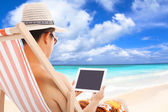 Relaxed man sitting on beach chairs and touching tablet — Stockfoto