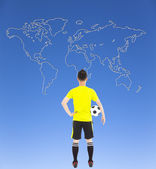 Soccer player holding a soccer and looking global map — Stock Photo