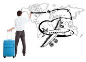 Young businessman drawing airplane and airline path on the map — Stock Photo