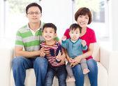 Feliz família asiática, sentado em um sofá de couro branco — Fotografia Stock