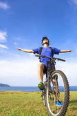 Close-up man sitting on a  mountain bike and open arms to relax — Stock Photo