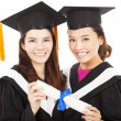 Two smiling young graduate students holding a diploma — Stock Photo #47689721