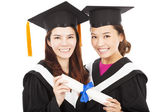 Two smiling young graduate students holding a diploma — Стоковое фото