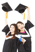 Two happy young graduate students holding hats and diploma — Stock Photo