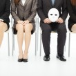 Business people waiting for job interview with a strange mask — Stock Photo