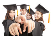Happy group graduate students point to the same direction — Stock Photo