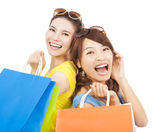 Happy young women with shopping bags — Stock Photo