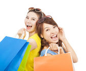 Happy young sisters with shopping bags — Stock Photo