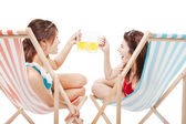 Two sunshine girl holding beer cheers  on a beach chair — Stock Photo