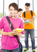 Pretty young student holding books and earphone with classmates — Stock Photo