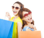 Young sisters holding shopping bags and Back to back — Stock Photo