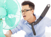 Young man cooling face under wind of fan — Stock Photo