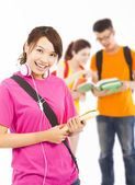Smiling young student holding books and earphone with classmates — Stock Photo