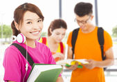 Young student holding books and earphone with classmates — Stock Photo