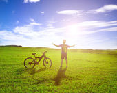 Backpacker standing next to bicycle with sunrise background — Stock Photo
