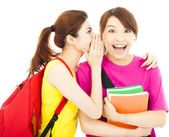 Pretty young girls whisper gossip to her classmate — Stock Photo