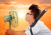 The heat wave is coming,business man holding a  electric fan — 图库照片