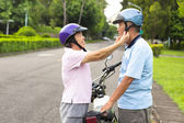 Happy grandmother help grandfather to wear a helmet — Stock Photo