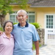 Happy asian senior couple standing in front of a house — Stock Photo #49068643