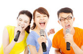 Happy young group having fun singing with karaoke — Stock Photo