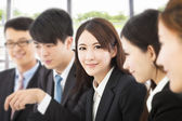 Shot of focus on young business woman with colleagues — Stock Photo