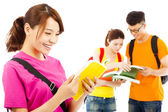 Young student read a  book  with classmates — Stock Photo