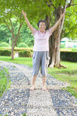 Happy grandmother standing on stone walkway and raise hands — Stock Photo