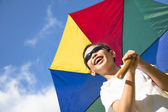 Happy little boy hold a colorful umbrella with blue sky  — Stock Photo