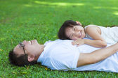 Father and daughter lying on a meadow in the park — Stock Photo