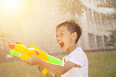 Little boy shouting and playing water guns in the park — Stock Photo