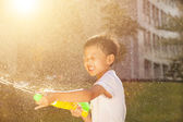 Cheerful little boy playing water guns in the park — Stock Photo