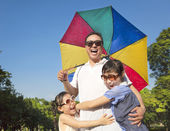 Father holding a colorful umbrella and hug two daughter — Stock Photo
