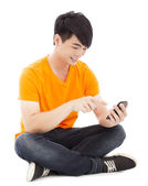 Smiling young student sitting on floor and touching smartphone — Stock Photo