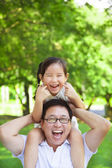 Girl sitting father shoulder and make a funny facial expression — Stock Photo