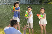 Little guys using water guns to spray their father — Stock Photo