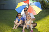 Father and two daughters sitting on a meadow with colorful umbre — Stock Photo