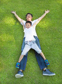 Happy father and son lying on a meadow together — Stock Photo
