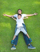 Young father and son lying on a meadow together — Stock Photo